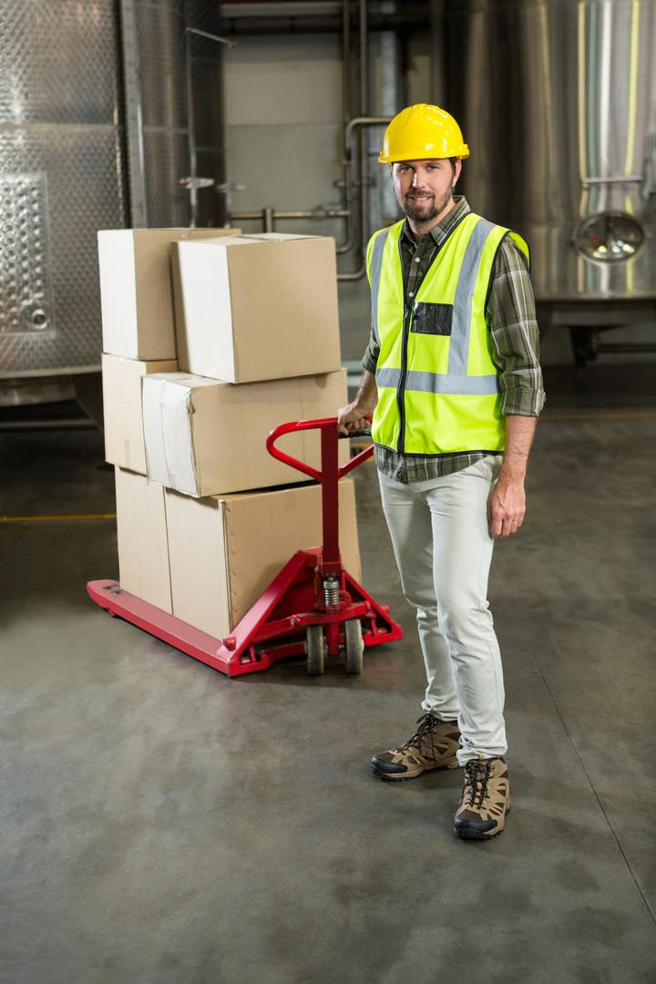 Full length portrait of male worker pulling trolley in warehouse Free Stock Images from PikWizard
