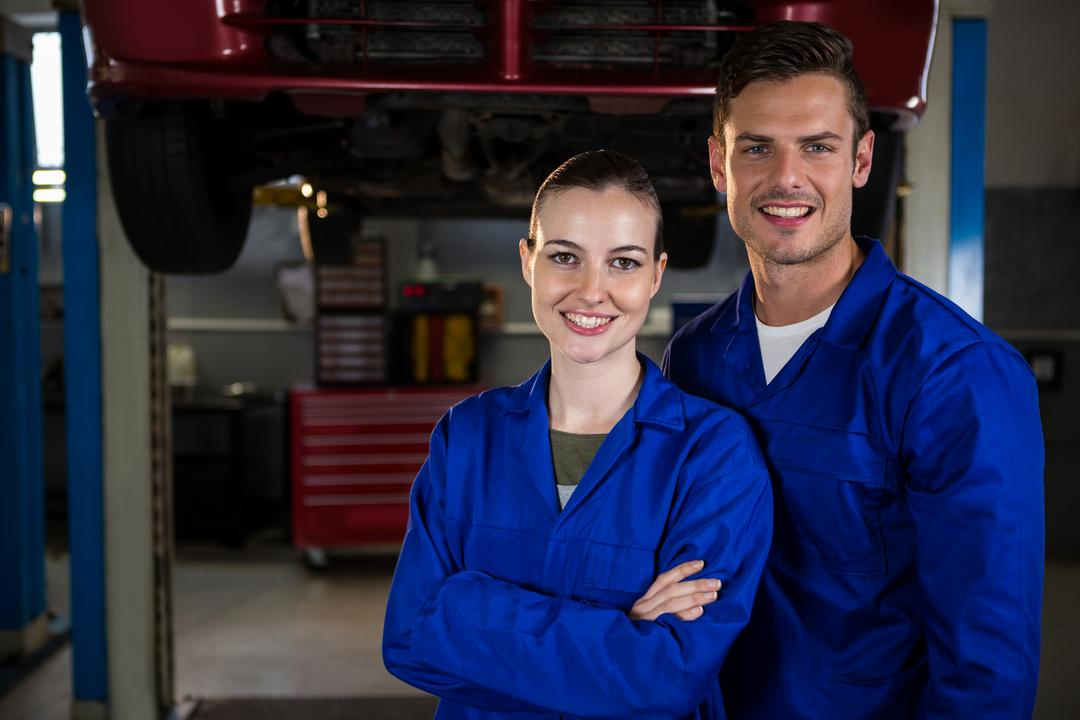 Portrait of happy mechanics standing with arms crossed under a car at repair garage
