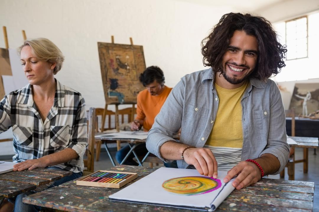 Portrait of smiling man practicing drawing while sitting with friends in art class Free Stock Images from PikWizard