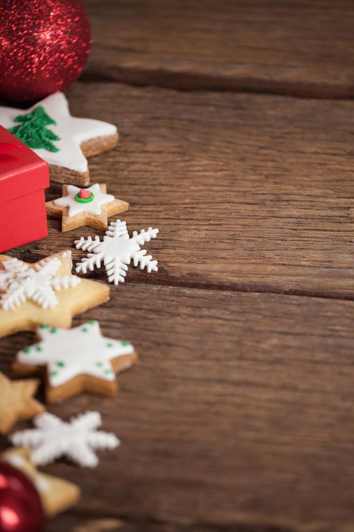 Cookies and christmas decorations on wooden table during christmas tree