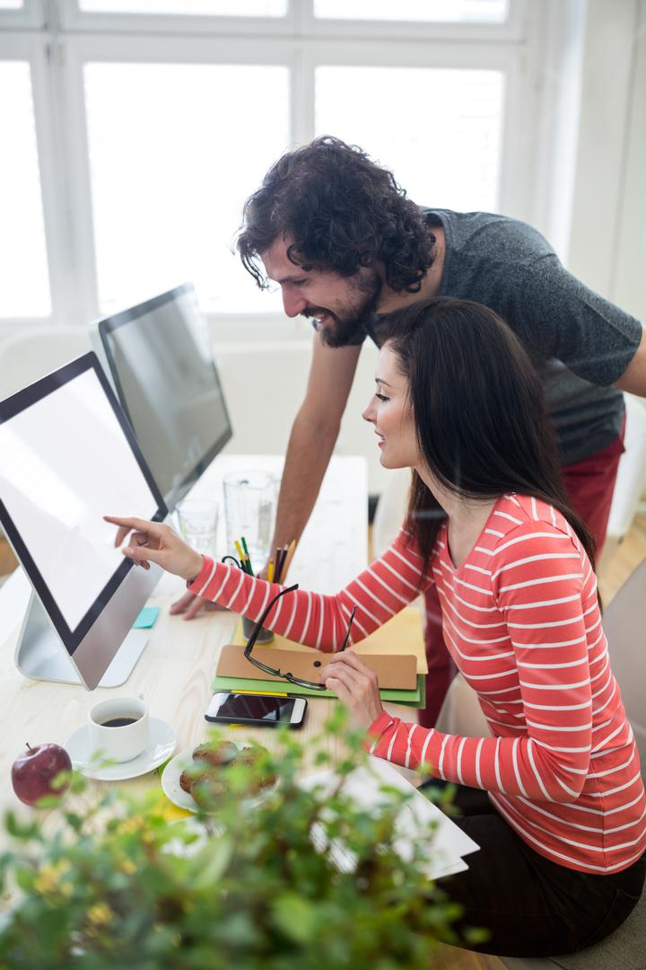 Male and female graphic designers interacting over computer in office