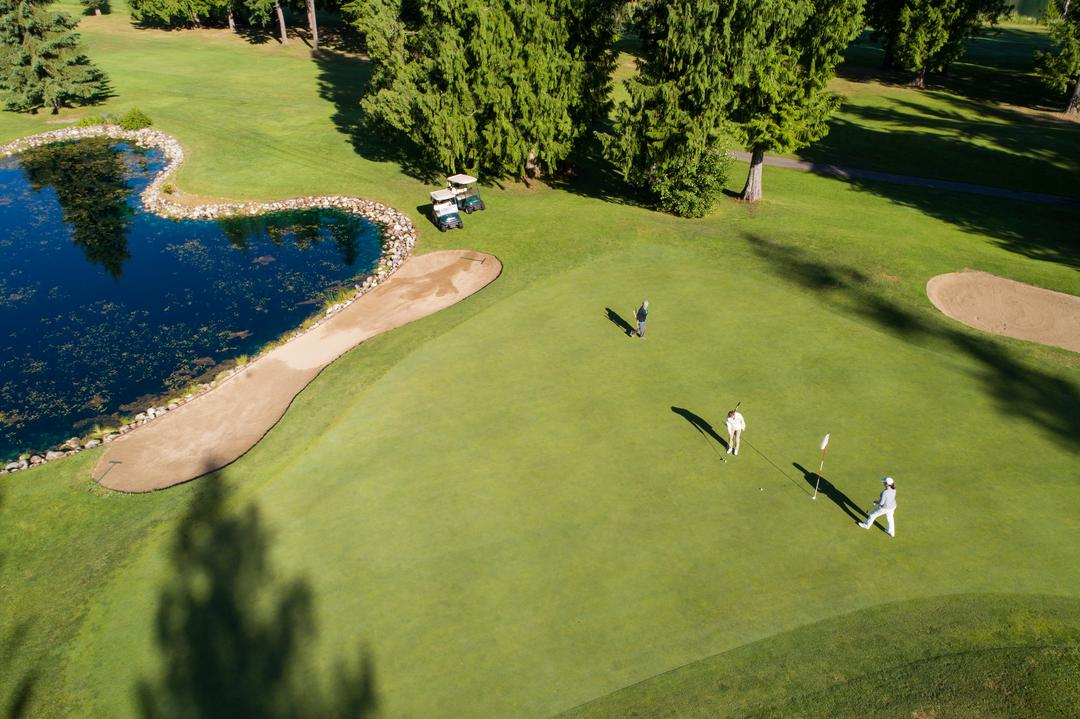 Ariel view of golfers in beautiful golf course on a sunny day Free Stock Images from PikWizard