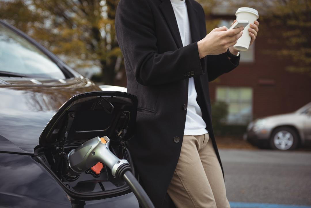Mid section of man using mobile phone while charging car at electric vehicle charging station
