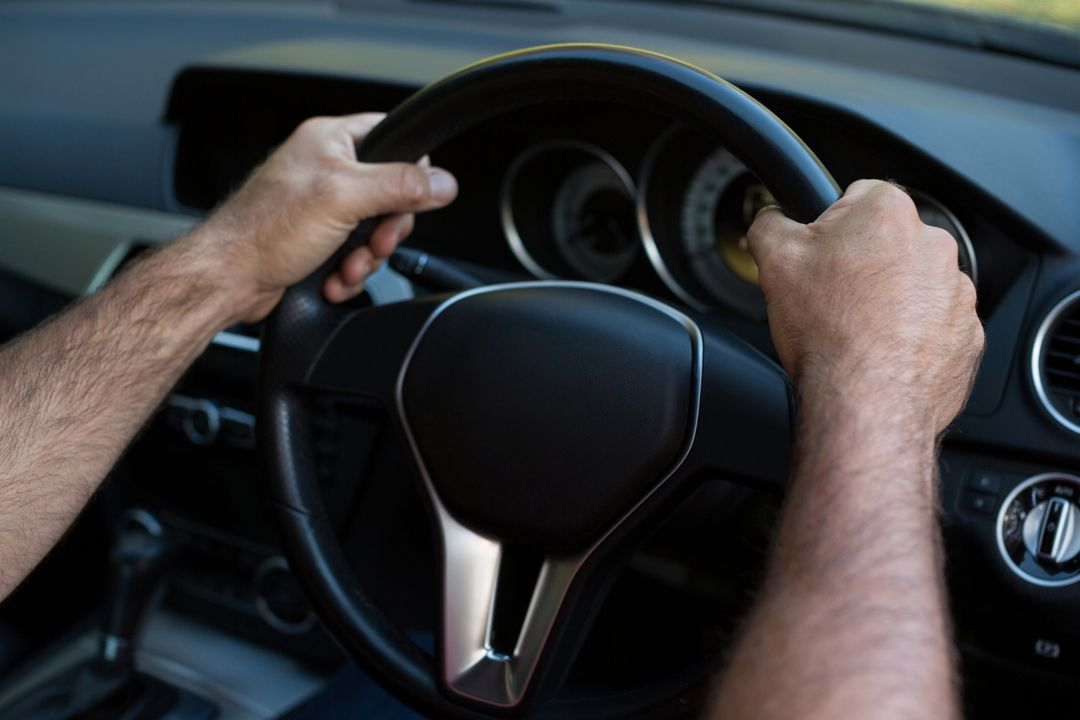 Cropped hands of person driving car Free Stock Images from PikWizard