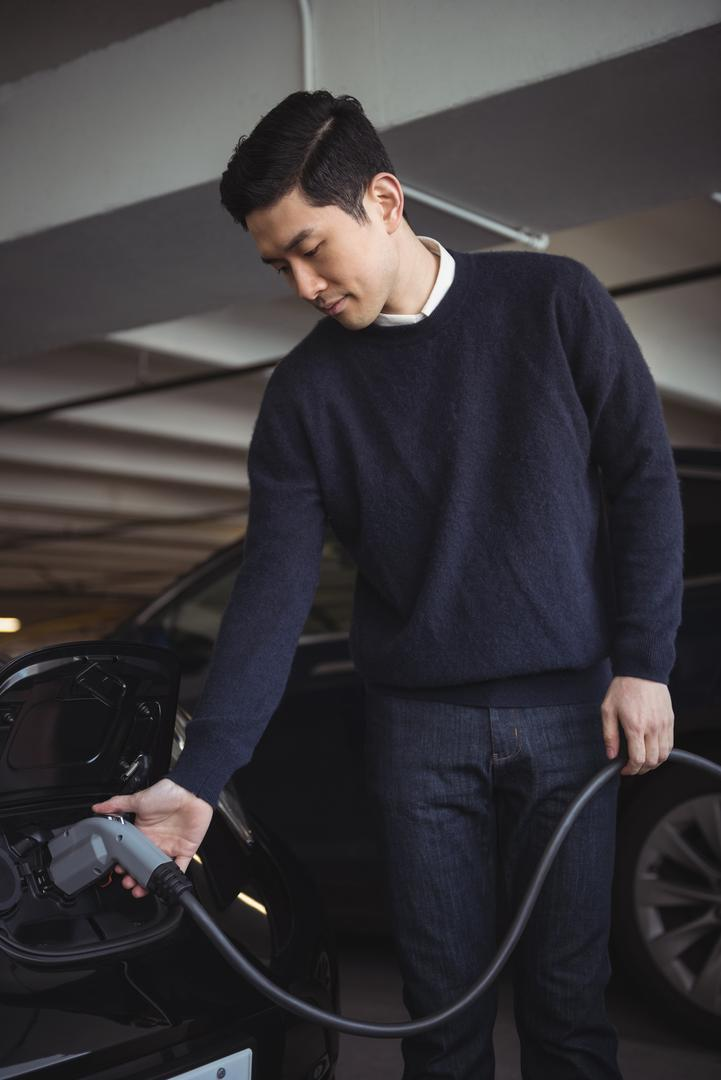 Handsome man charging car at electric vehicle charging station Free Stock Images from PikWizard