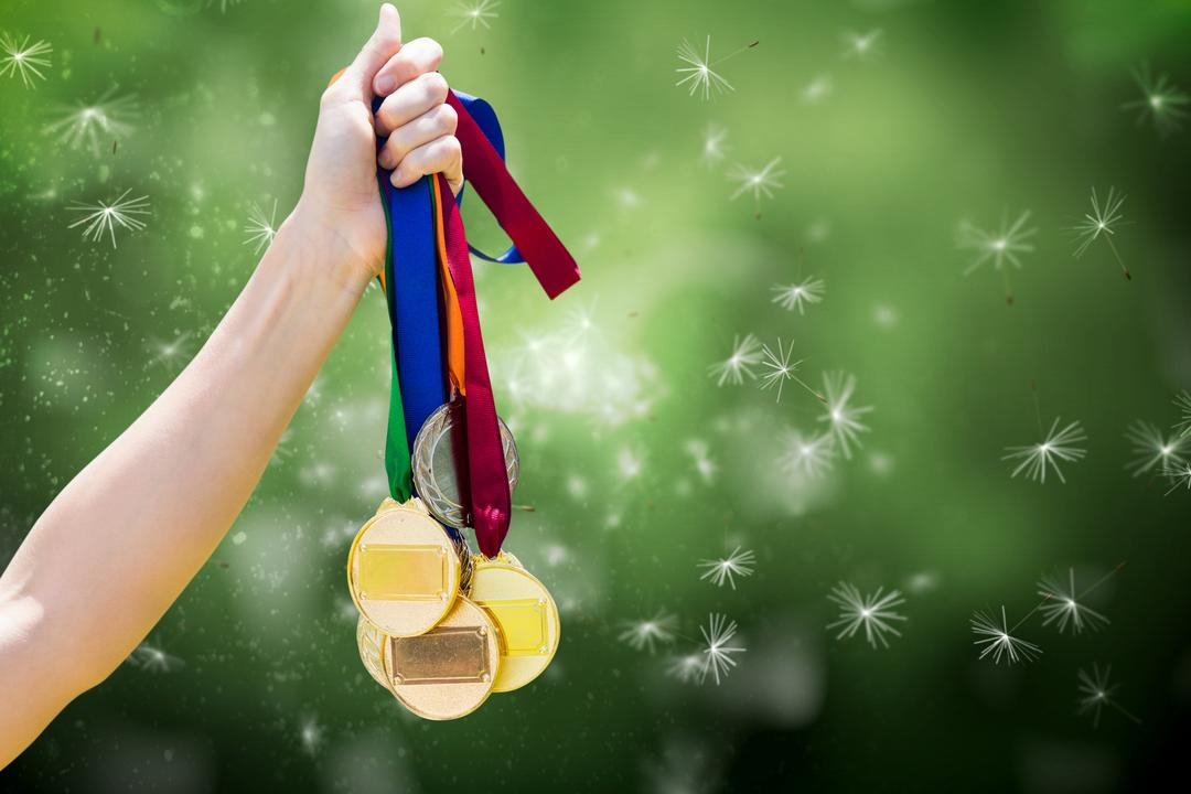 Composite of hand holding medals over nature background