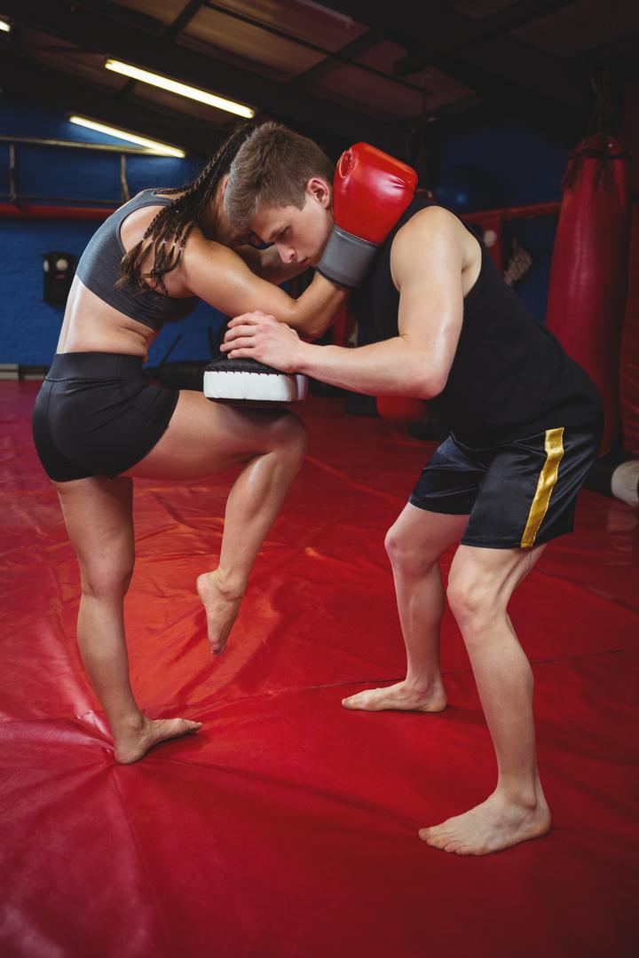 Female boxer practicing with trainer
