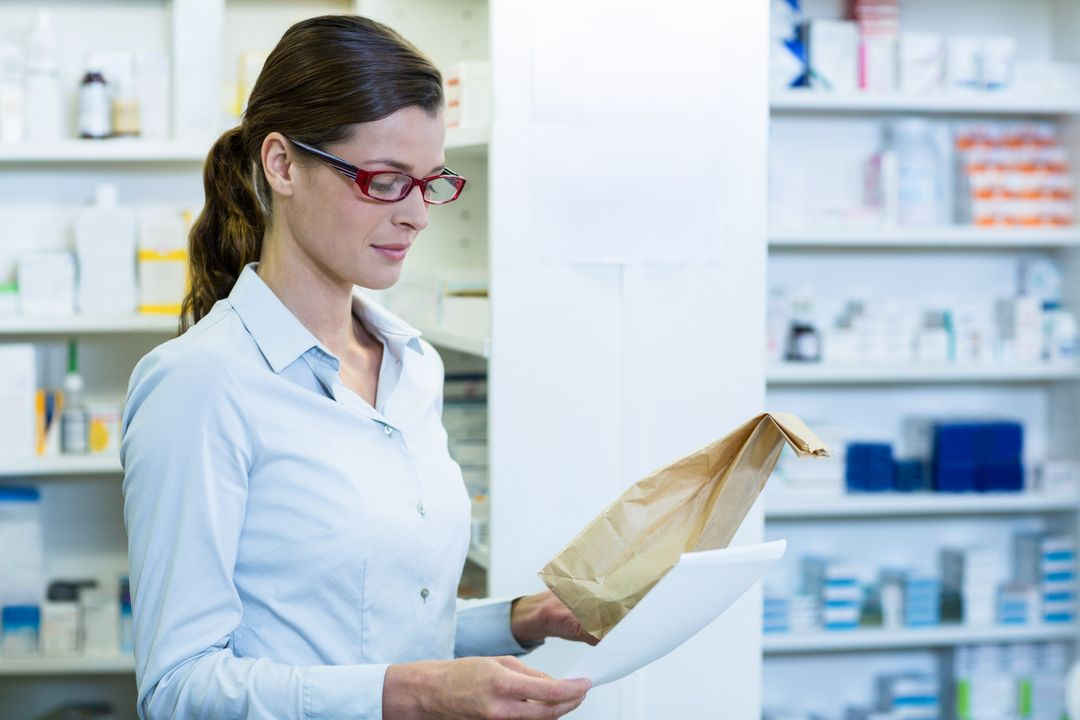 Pharmacist checking prescription and medicine package in pharmacy Free Stock Images from PikWizard
