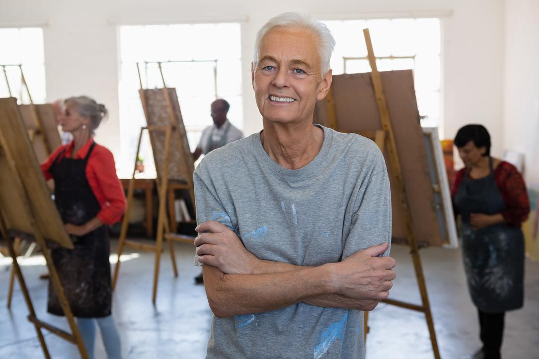 Portrait of senior man with crossed standing in art studio with artists painting in backgorund Free Stock Images from PikWizard