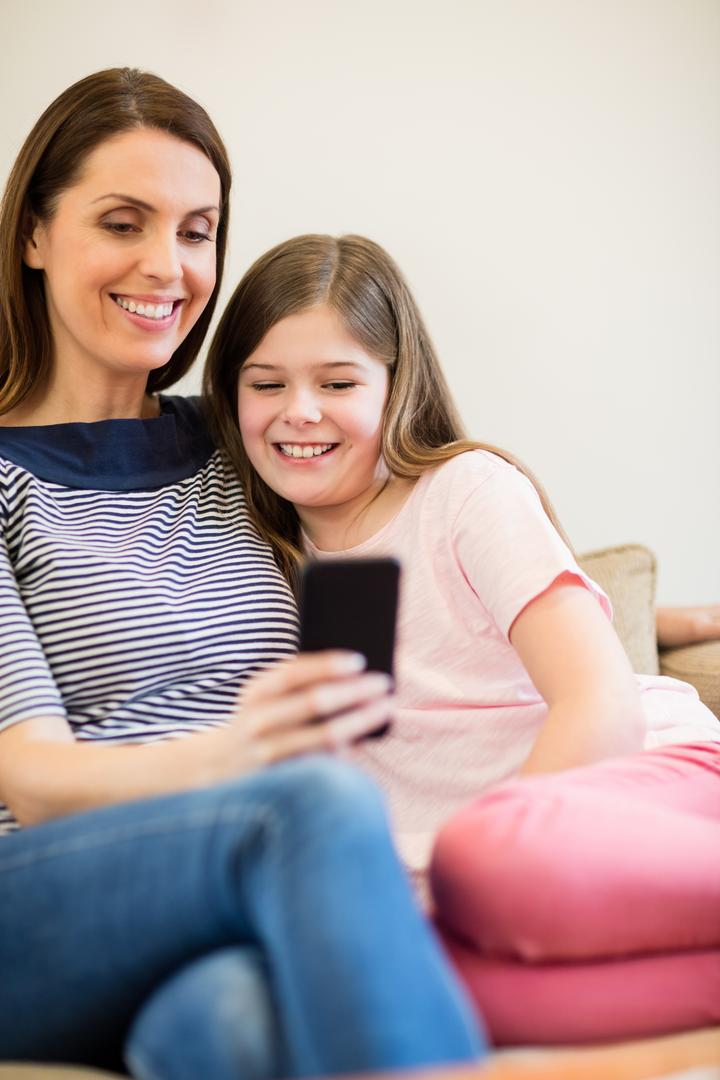 Mother and daughter using mobile in living room at home