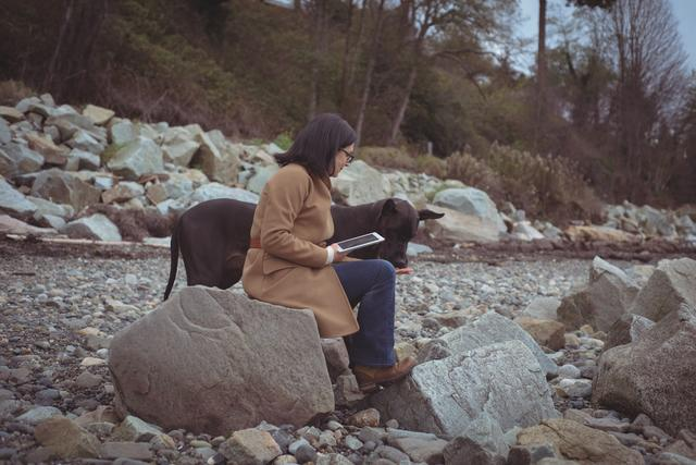 Woman holding digital tablet by dog at beach