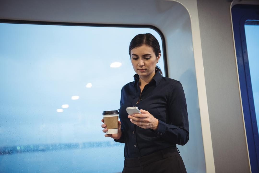 Beautiful businesswoman with coffee cup using phone while standing in train