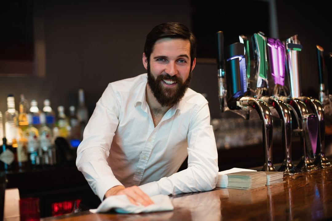 Portrait of smiling bartender cleaning bar counter at bar