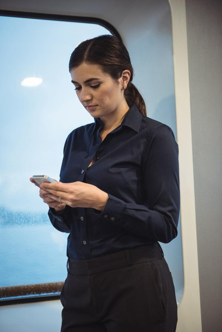 Businesswoman using phone while standing in train