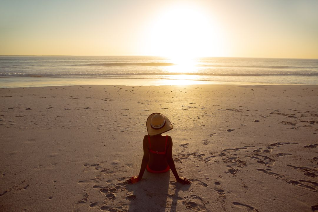 Rear view of woman in hat relaxing on the beach