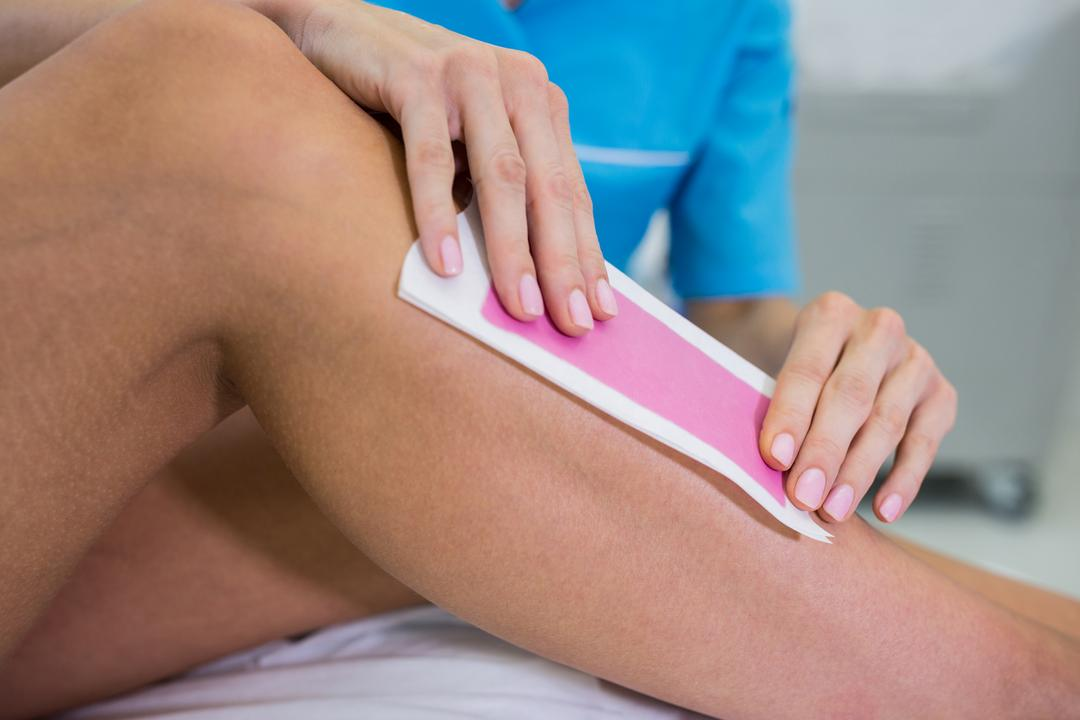 Woman getting her leg hair removed at beauty salon