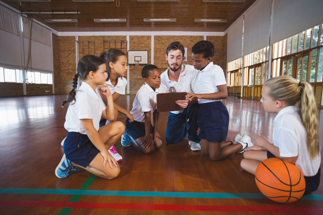 Sport teacher and school kids discussing on clipboard in basketball court at school gym Free Stock Images from PikWizard