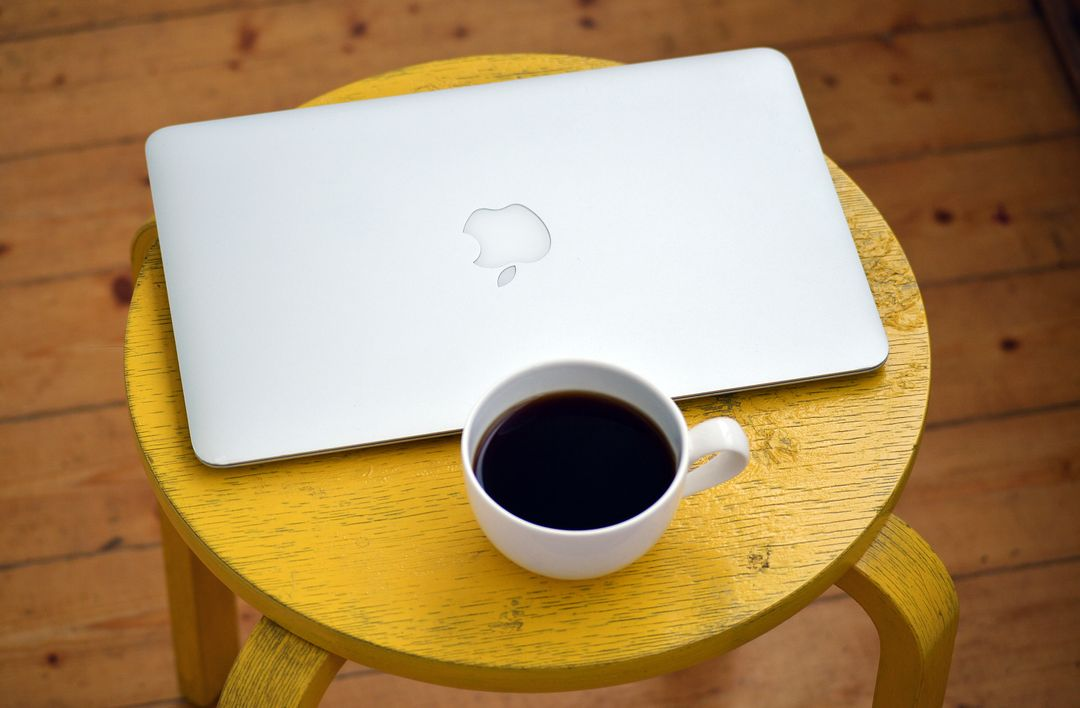 Overhead image of a Macbook on a yellow stool with coffee
