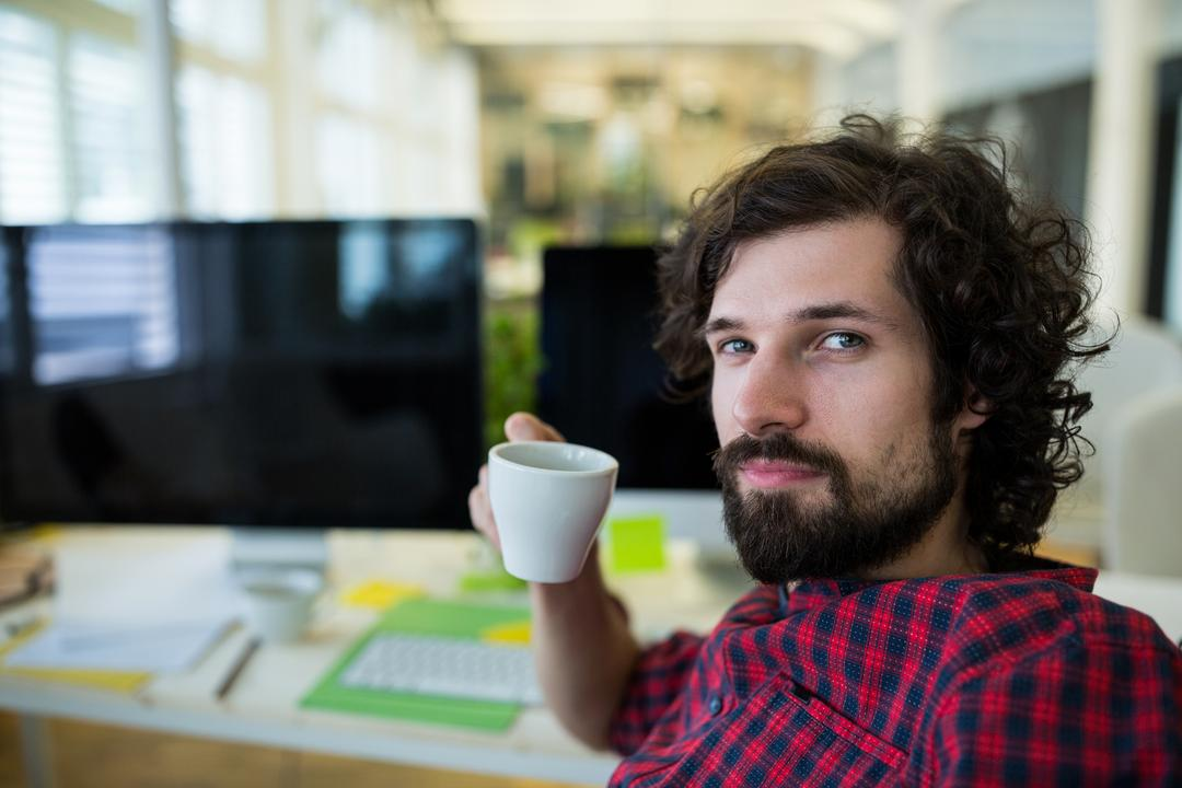 Male graphic designer having coffee in office