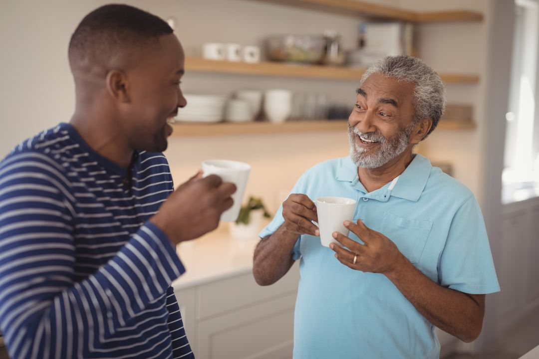 Smiling father and son interacting while having cup of coffee at home