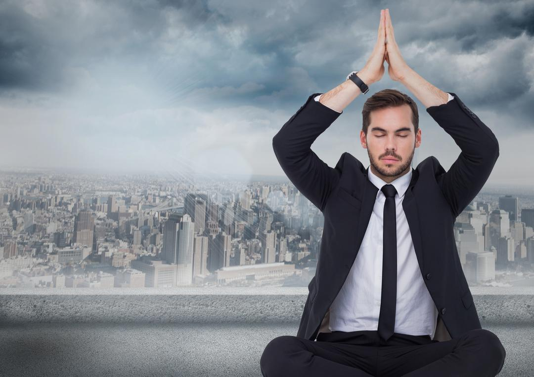 Digital composite of Business man with hands over head meditating against grey skyline and clouds Free Stock Images from PikWizard