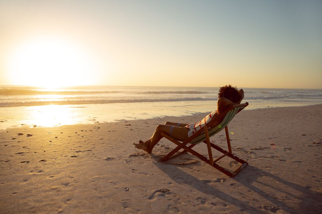 Man relaxing with hands behind head in beach chair on the beach Free Stock Images from PikWizard