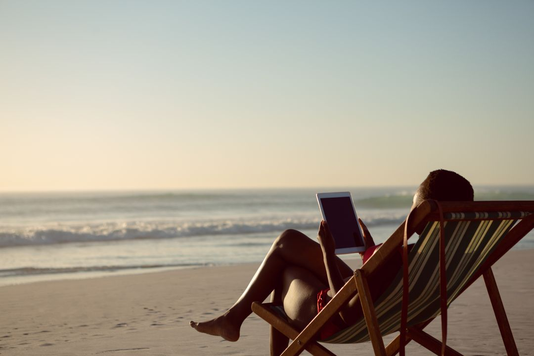 Rear view of woman using digital tablet while relaxing in a beach chair on the beach