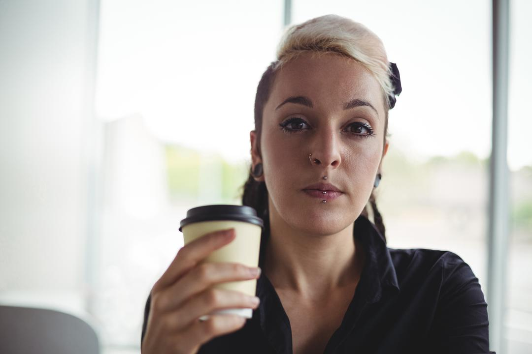 Portrait of woman holding disposable coffee cup in café Free Stock Images from PikWizard