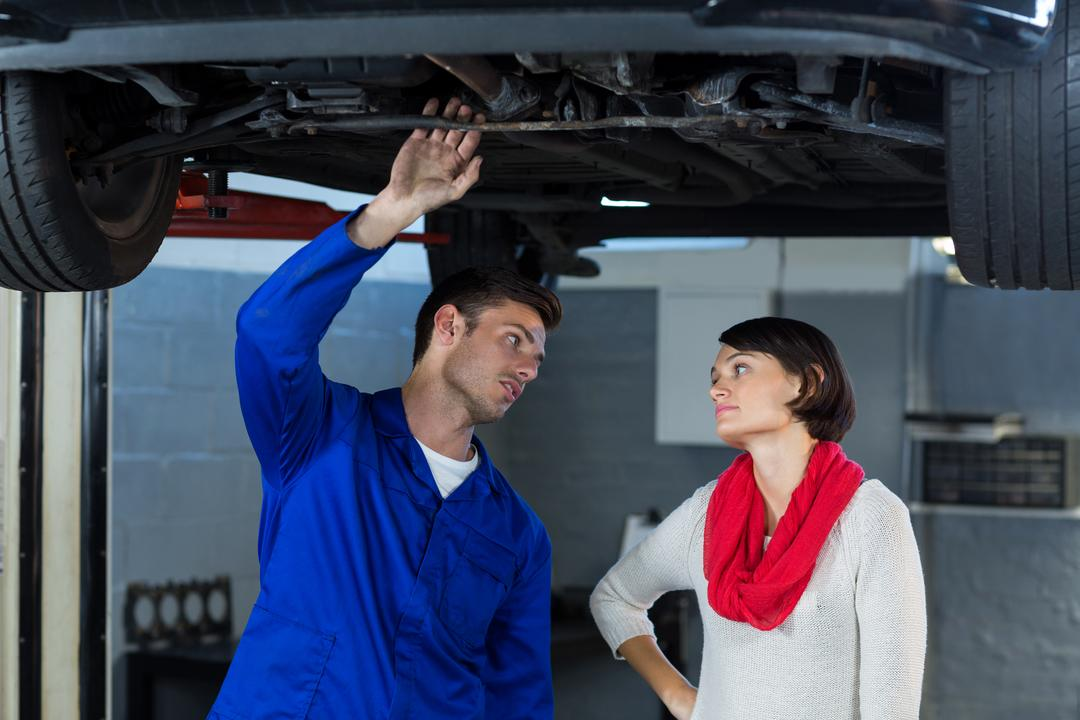 Mechanic showing customer the problem with car in repair garage Free Stock Images from PikWizard