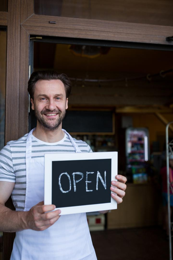 Portrait of smiling owner holding a open sign at bakery shop entrance