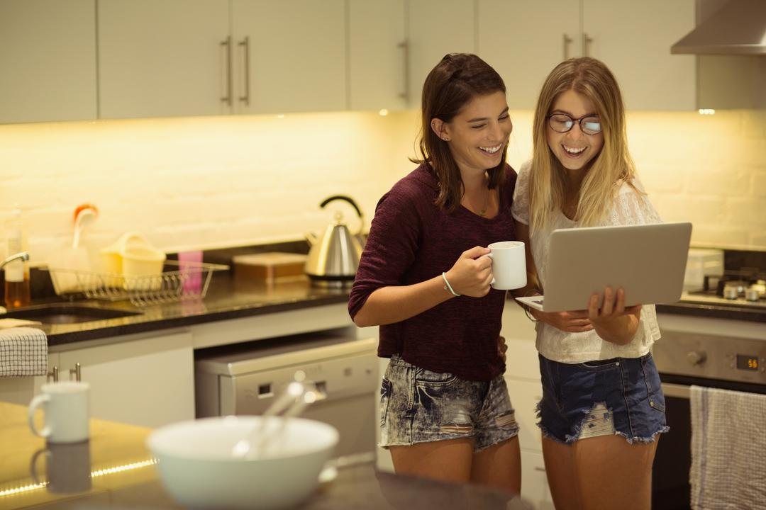 Image of Two Woman Standing in the Kitchen and Watching Something on a Laptop