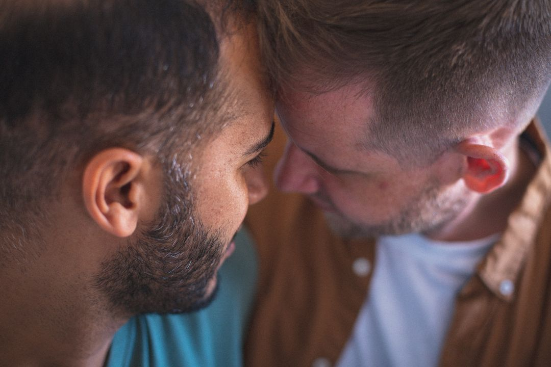 Gay couple embracing with hands together