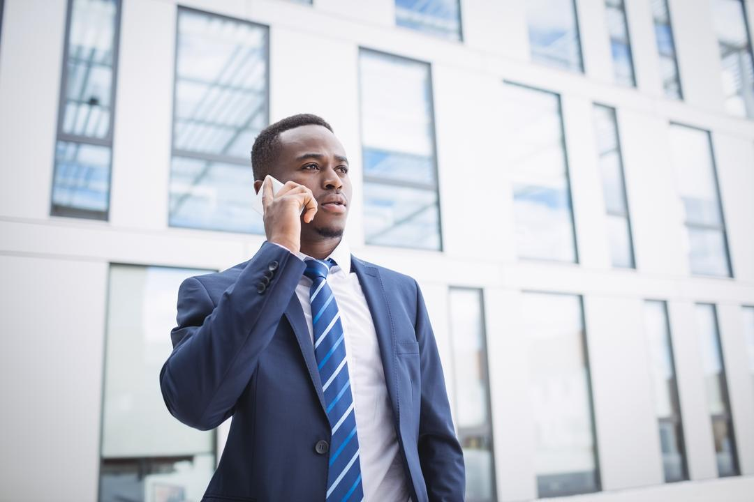 Businessman talking on mobile phone outside office building