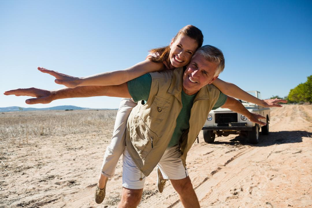 Portrait of happy playful couple on landscape during sunny day Free Stock Images from PikWizard