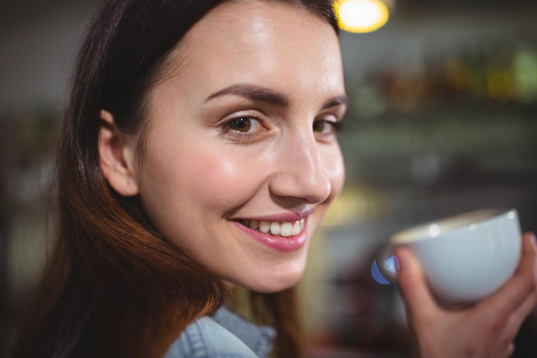 Portrait of beautiful woman having a cup of coffee in café