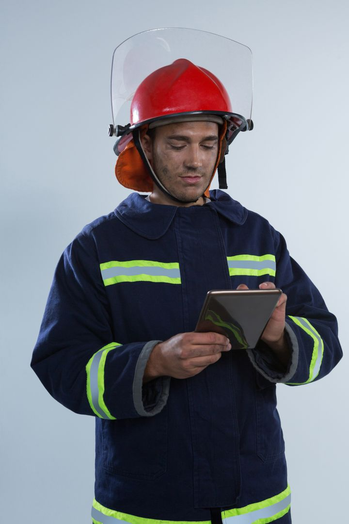 Smiling fireman using digital tablet against white background Free Stock Images from PikWizard