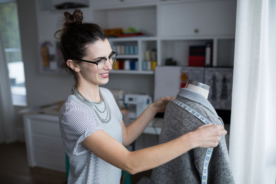 Fashion designer taking measure of fabric at home