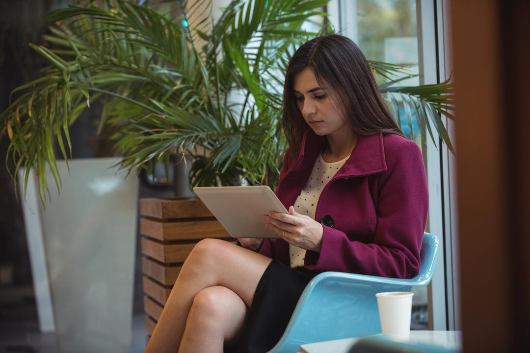 Beautiful businesswoman using digital tablet in café