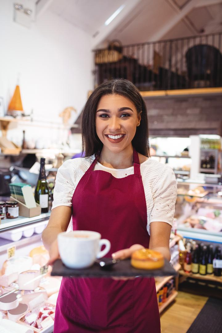Portrait of smiling waitress holding a cup of coffee and snacks in super market