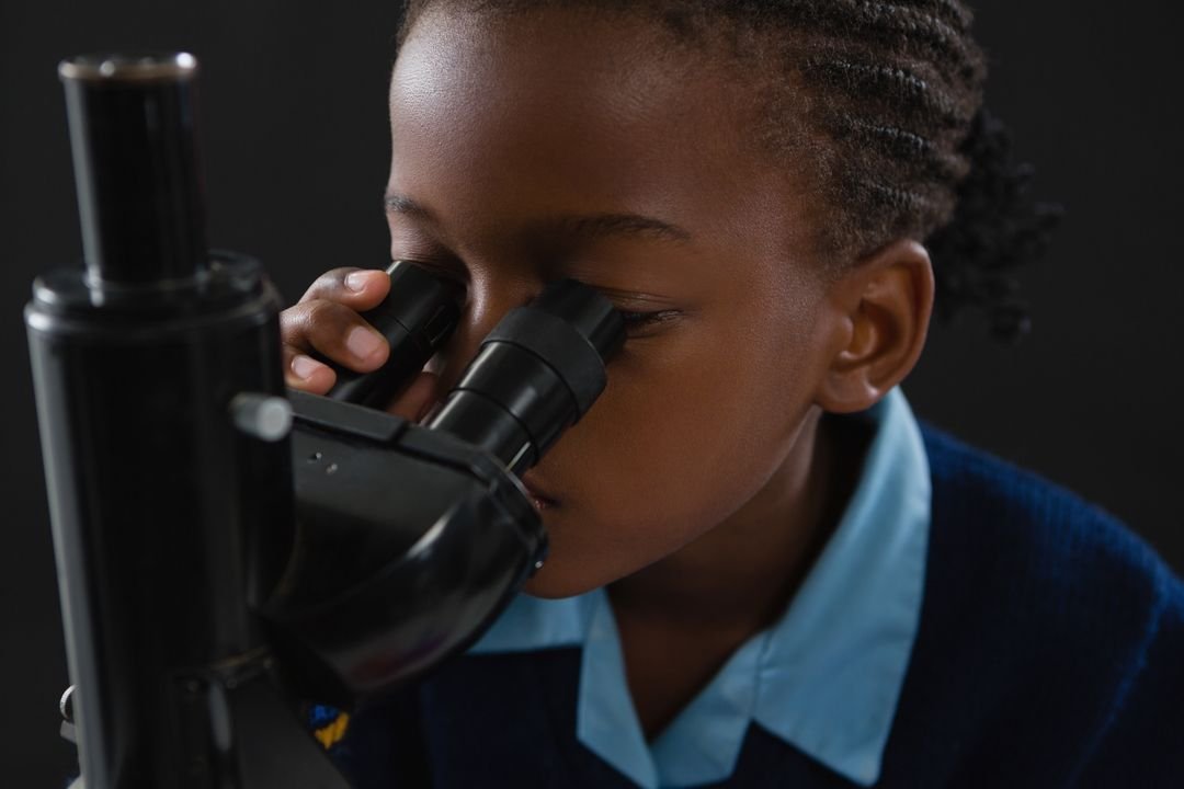 Attentive schoolgirl using microscope against black background Free Stock Images from PikWizard