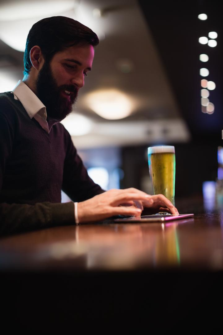 Man using digital tablet with glass of beer on counter in bar