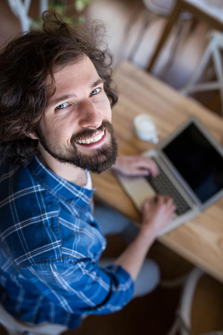 Portrait of smiling man looking up while using laptop in coffee shop Free Stock Images from PikWizard