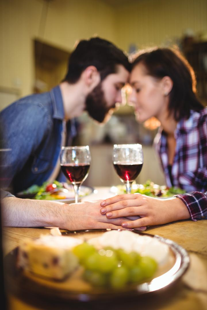 Couple romancing while having wine and breakfast at home