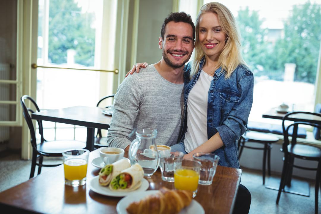 Portrait of smiling couple sitting with arms around in café Free Stock Images from PikWizard