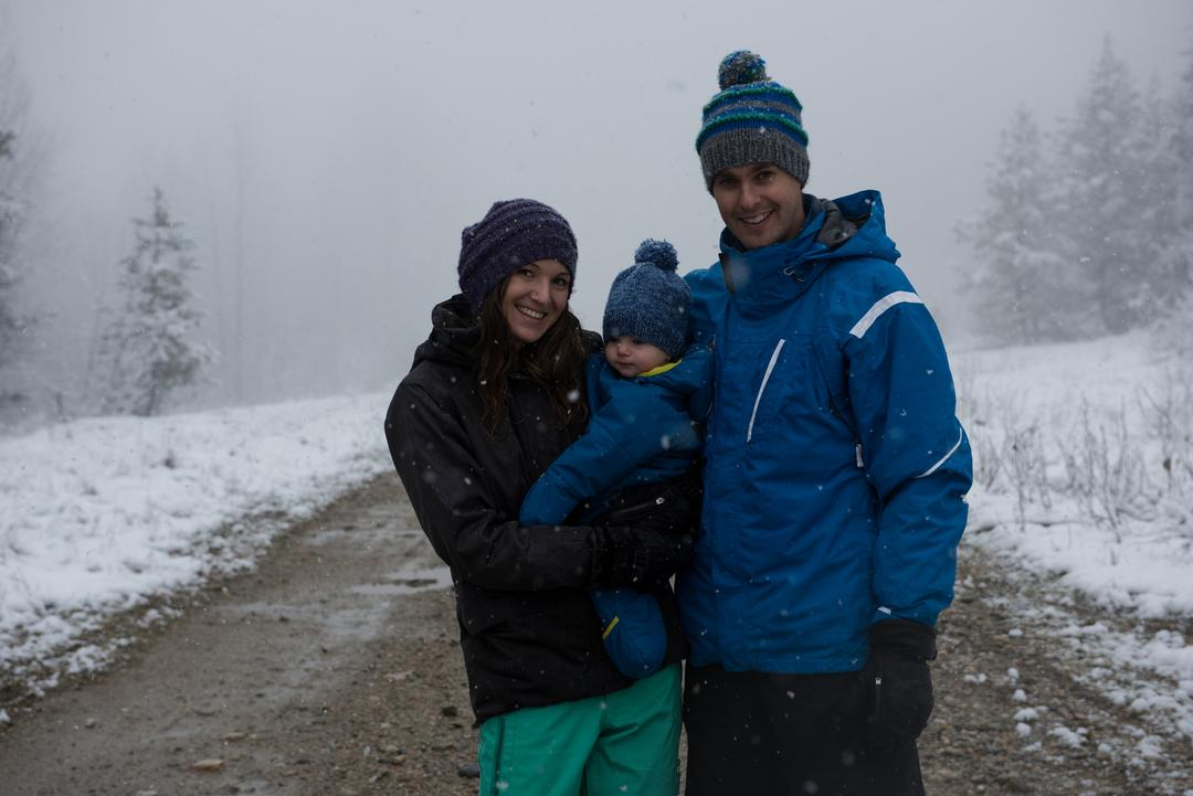 Portrait of happy parents with son standing on road during winter