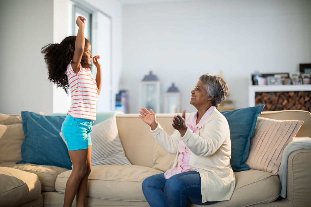 Grandmother applauding her granddaughter while dancing in living room at home