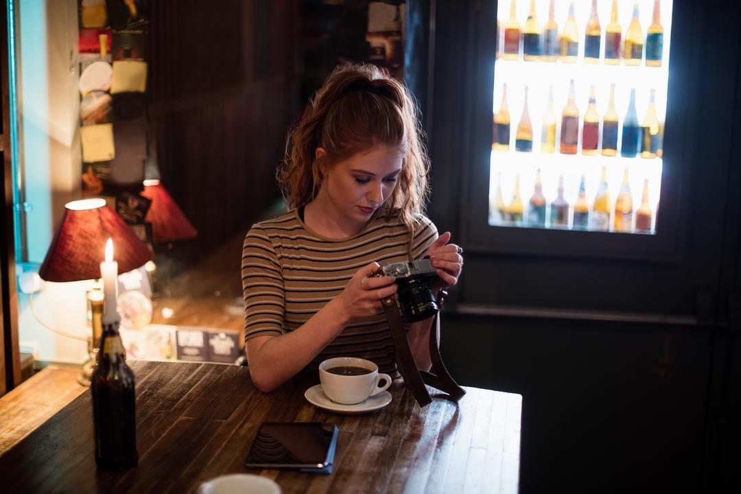 Beautiful woman checking photos in digital camera at bar