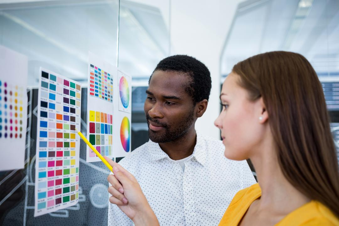 Male and female graphic designers interacting over color chart in office