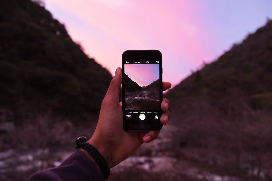 Image of a hand taking a photo of a pink sunset on a black iPhone,