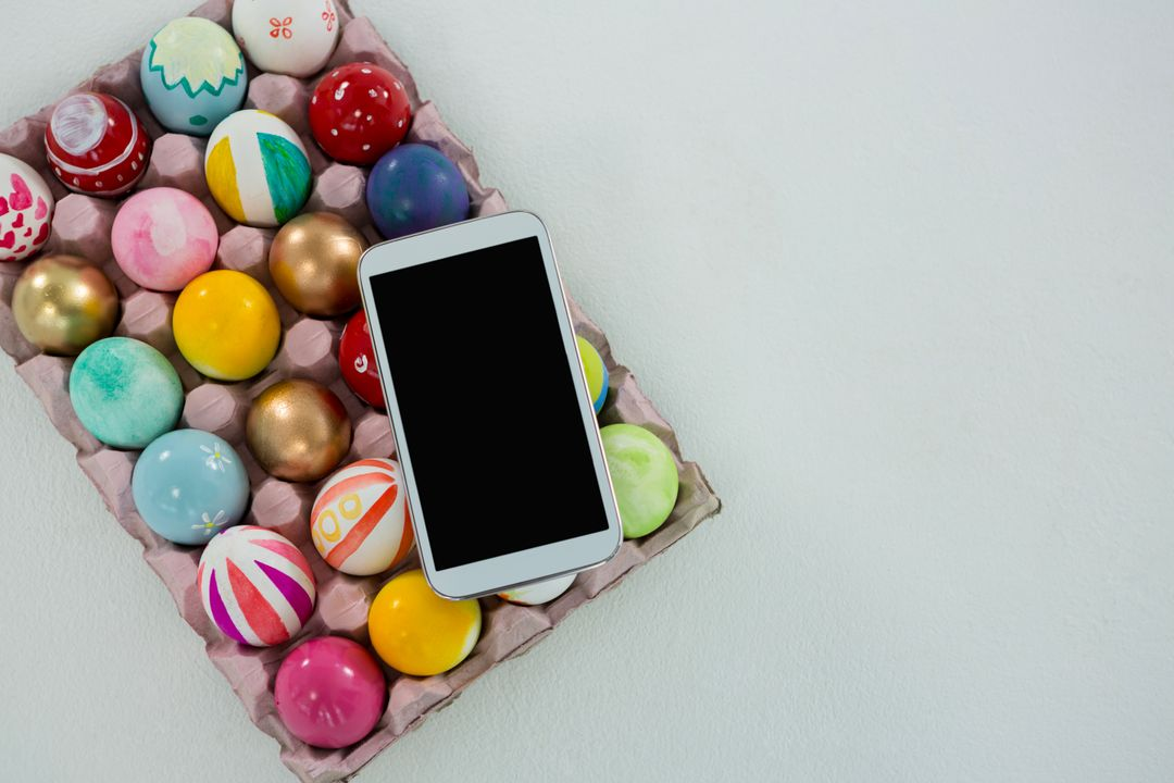 Mobile kept on painted Easter eggs in egg carton on white background Free Stock Images from PikWizard